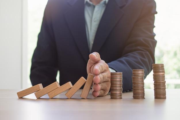 Защита финансов от концепции эффект домино. руки останавливают эффект домино, прежде чем уничтожить стопку денег. Premium Фотографии