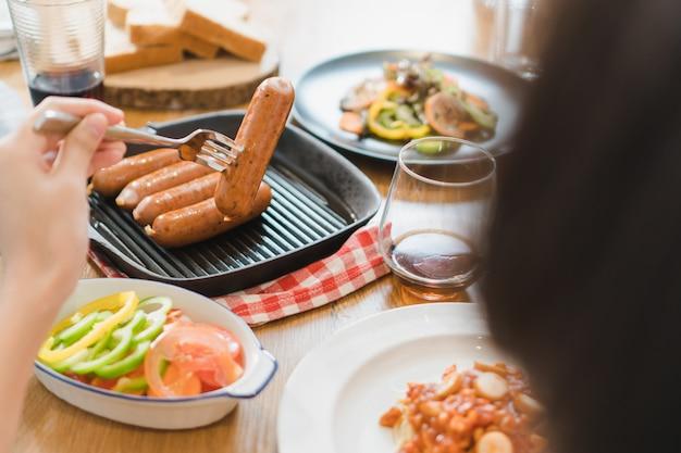 木製のテーブルの上に食べ物や友達一緒に夕食を食べての様々な。 Premium写真
