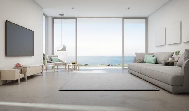 大きなガラスのドアと木製テラス付きの豪華な夏のビーチハウスの海ビューリビングルーム。 Premium写真
