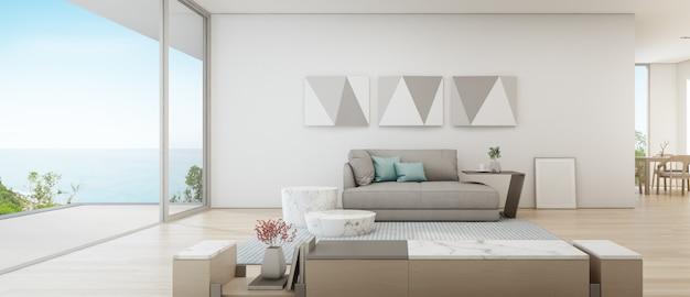 木製テラスの近くに大きなガラスのドアが付いている豪華な夏のビーチハウスのシービューダイニングとリビングルーム。 Premium写真
