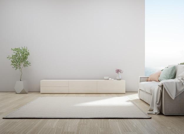 Гостиная с видом на море роскошного летнего пляжного домика с подставкой под телевизор и деревянным шкафом. Premium Фотографии