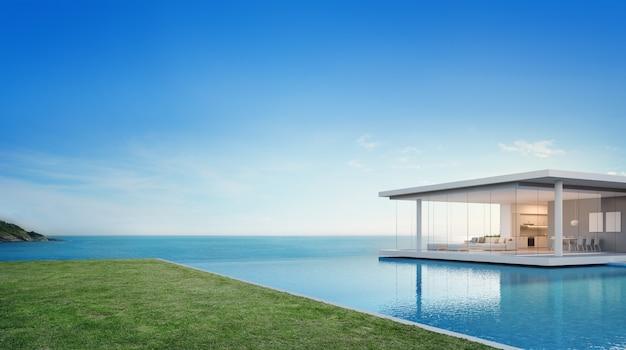 モダンなデザインの空の草の床のデッキの近くの高級ビーチハウスと海ビューのスイミングプール。 Premium写真