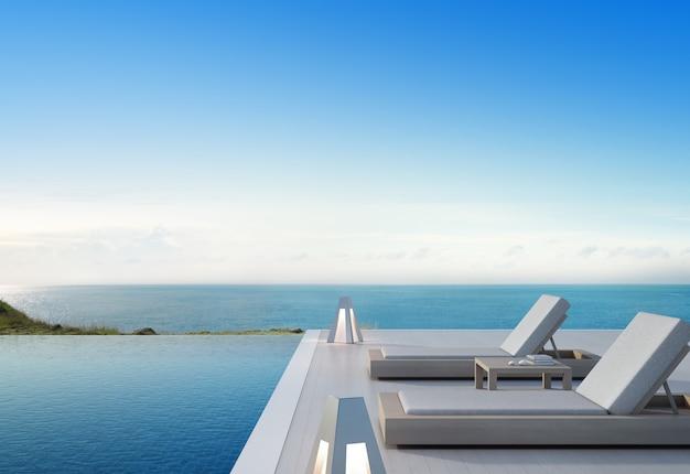 Бассейн с видом на море и терраса в современном роскошном пляжном доме с голубым небом Premium Фотографии