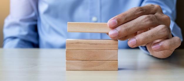 木製ビルディングブロックを持っているビジネスマン手 Premium写真