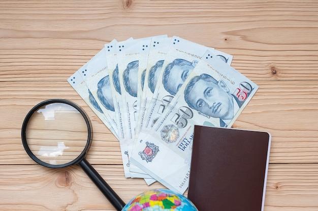 パスポート、虫眼鏡、木製テーブルの上の世界とお金の紙幣 Premium写真