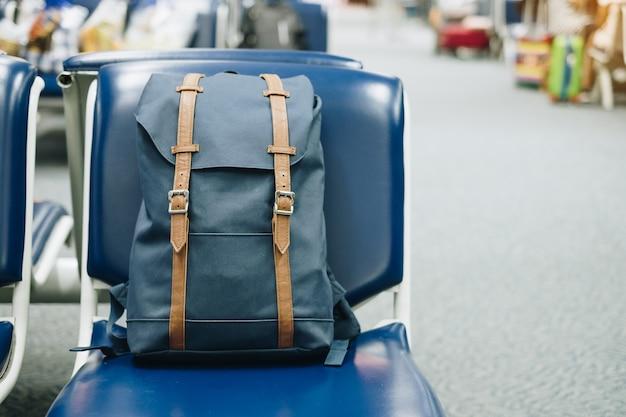 Голубая винтажная сумка на месте на интерьере крупного аэропорта. путешествие и обратно в школу Premium Фотографии
