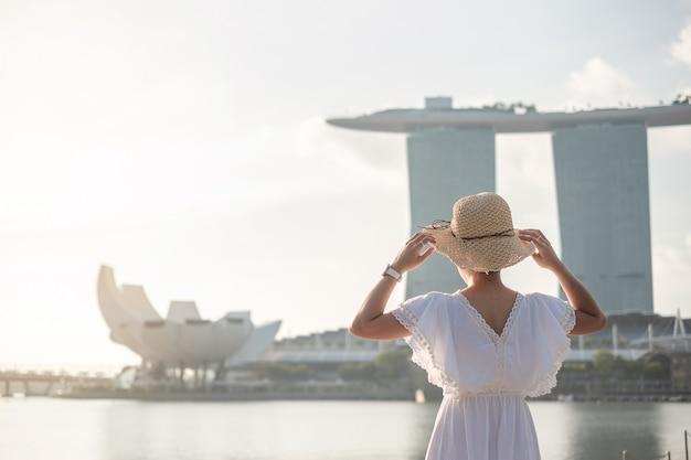Молодая женщина путешествуя с шляпой в утре, счастливое азиатское посещение путешественника в центре города сингапура. ориентир и популярный для туристических достопримечательностей. азия трэвел концепция Premium Фотографии
