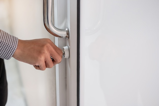 オフィスのドアを開けるドアノブのロックを解除する実業家 Premium写真