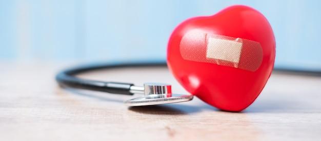 赤いハート形の聴診器。医療、保険、世界心臓デーのコンセプト Premium写真
