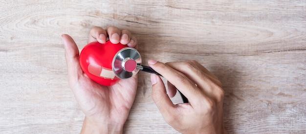 木製の背景に赤いハート形の聴診器を持つ女性の手。 Premium写真