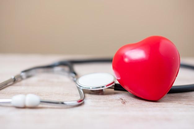 赤いハート形の聴診器。ヘルスケアと世界心臓デーのコンセプト Premium写真