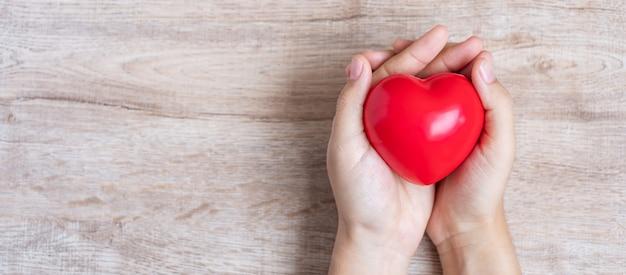 木製の赤いハート。ヘルスケア、および世界心臓デーのコンセプト Premium写真