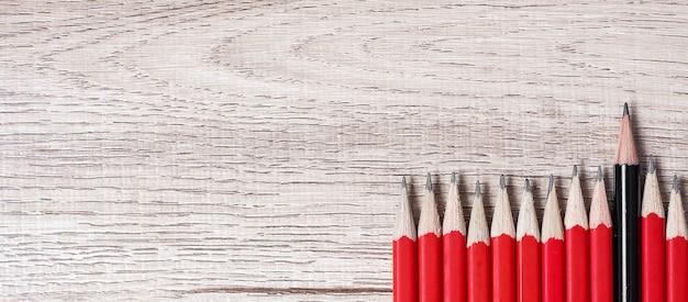 Черный карандаш отличается от толпы красных карандашей. Premium Фотографии