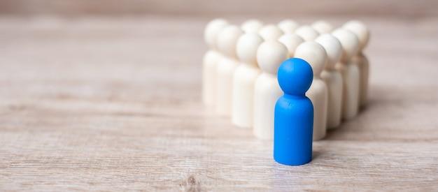 木製の男性の群衆の中に青いリーダービジネスマン。リーダーシップ、ビジネス、チーム、チームワーク、人事管理 Premium写真