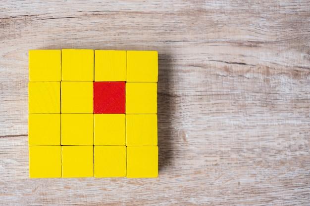 黄色のブロックの群衆とは異なる赤いキューブブロック Premium写真