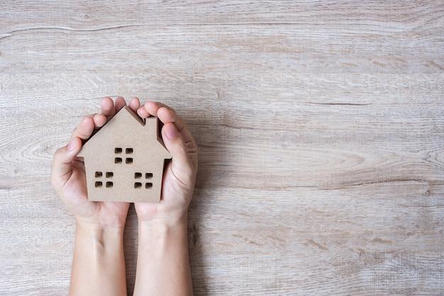 Руки держат модель дома на фоне дерева таблицы с копией пространства. Premium Фотографии