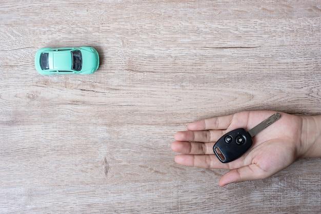車のキーを保持している男の手。銀行、保険、金融、現金のための車 Premium写真