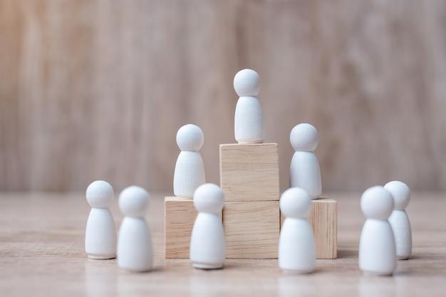 木製の男性の群衆と実業家リーダーの上部を持っている手。 Premium写真