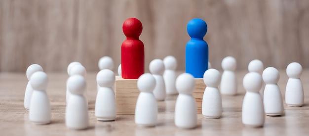 木製の従業員の群衆の中に赤と青の実業家リーダー。 Premium写真