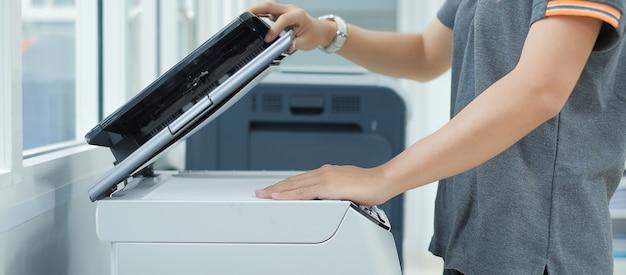 Ручная установка бумажной бумаги в лазерный копировальный аппарат для сканера принтера в офисе Premium Фотографии