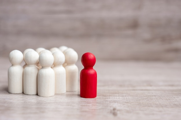 木製の男性の群衆の中に赤いリーダー実業家。リーダーシップ、ビジネス、チーム、チームワーク、人的資源管理の概念 Premium写真
