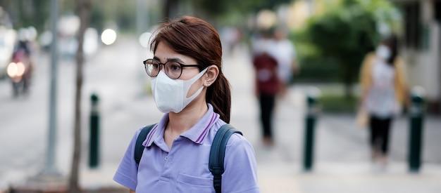 Маска предохранения от молодой азиатской женщины нося против вируса гриппа в городе. здравоохранение и концепция загрязнения воздуха Premium Фотографии
