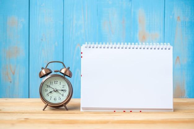 ノートブック、レトロな目覚まし時計、テーブルとコピースペース。目標、ミッション、新しいスタートコンセプト Premium写真