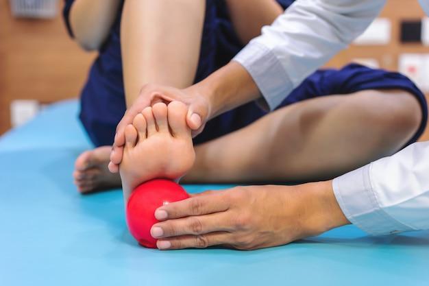 Физиотерапевты дают советы пациентам по использованию мяча для уменьшения боли на подошвах ног. Premium Фотографии