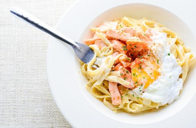 サーモン、卵、パルメザンチーズのフェットチーネ、白いプレートで提供しています。 Premium写真