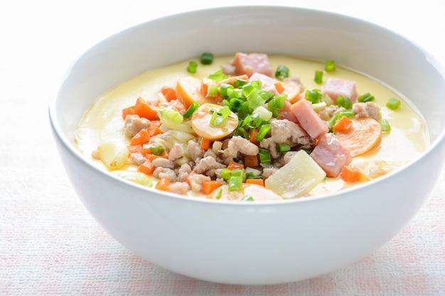 Кухня с заварным кремом на пару в белой миске с рубленой свининой Premium Фотографии