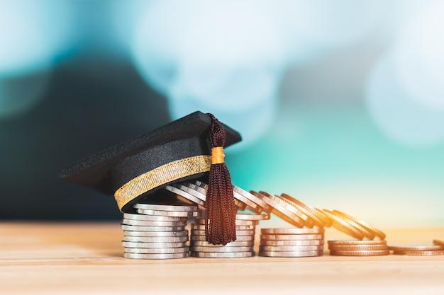木製テーブルの色の背景にコインの上のスタックにお祝いの卒業生 Premium写真