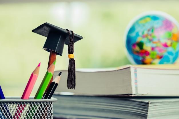教育卒業研究の概念:鉛筆上の黒卒業帽子、ぼやけヨーロッパ地球 Premium写真