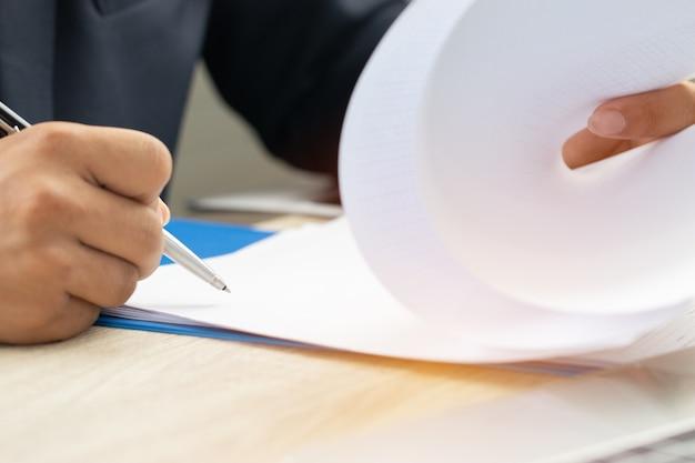 Азиатский бизнесмен менеджер по проверке и подписанию документов, заполняющих документы Premium Фотографии