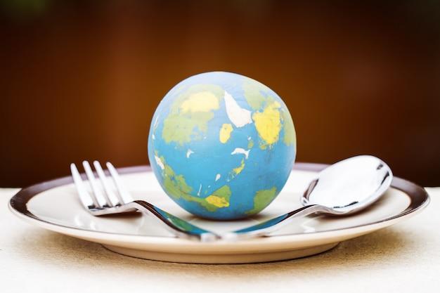 世界的なモデルは有名なホテルのサーブメニューのためのフォークスプーンが付いている版に置かれた。世界の料理 Premium写真