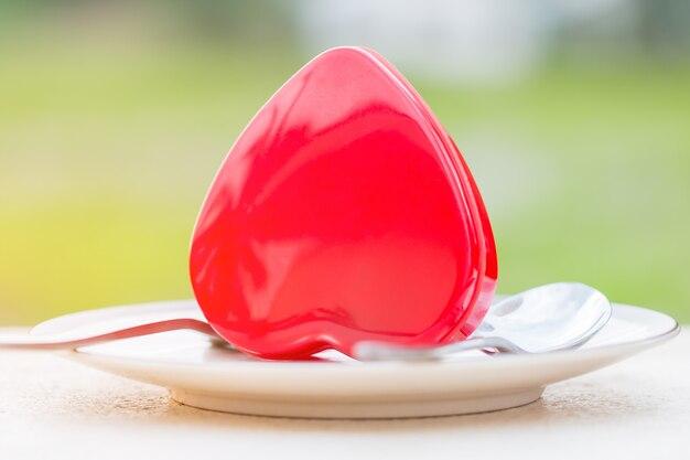 バレンタインの日の概念、有名なホテルのサーブメニューのフォークスプーンで皿に置かれた赤いハート Premium写真