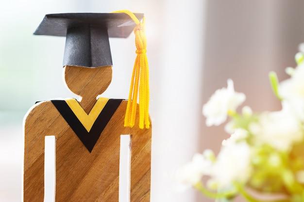 学校に戻る卒業おめでとうと花とキャップを祝う木材 Premium写真