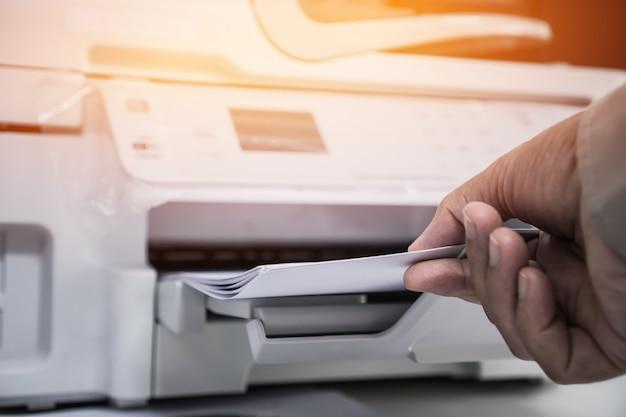 Руки коммерсантки работая в процессе прессе бумаги в лазерном принтере на занятом офисе стола работы Premium Фотографии