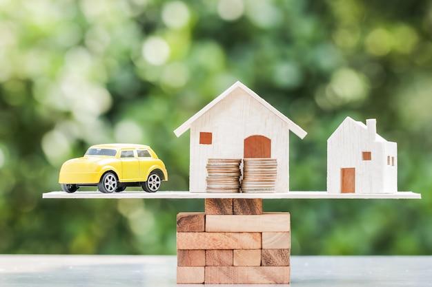ビジネス不動産投資の概念:木造住宅、お金のコインのスタックが付いている車 Premium写真