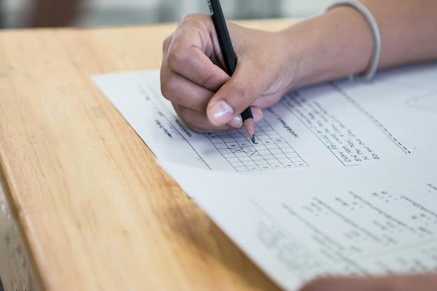 紙の解答用紙に鉛筆の筆記試験を保持している高校大学生 Premium写真