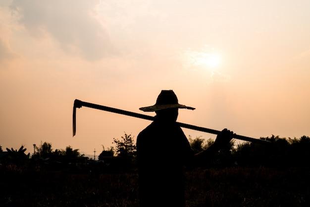 Черный силуэт работника или садовника, держа лопату на закате свет Premium Фотографии