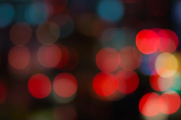 街の夜の明るい背景の道路上の抽象的な赤いボケライト Premium写真