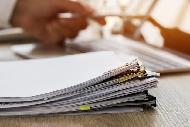 紙のファイルのスタックで作業するためのペンを持つビジネスマン手 Premium写真