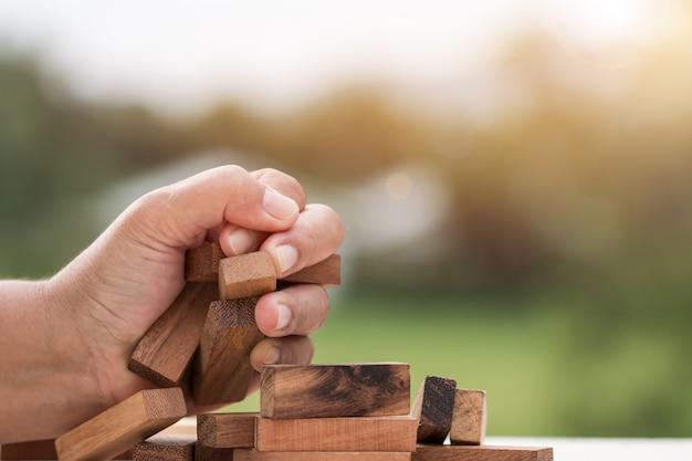 ビジネスマン握りしめ木製ドミノスクエアブロックタワー Premium写真