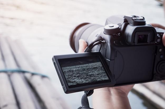 カメラマンは写真を撮るカメラの記録のための三脚にビデオカメラやプロのデジタル一眼レフを設定 Premium写真