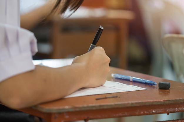 アジアの学生の手が試験を受ける、光学フォームテストに鉛筆を保持している試験を書く Premium写真