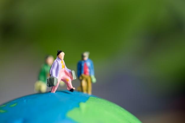 地球地球緑モデルの上に立って海外旅行の旅人のために旅行する若い旅行者のミニチュア置物グループ Premium写真