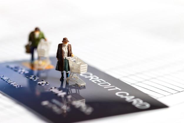 ミニチュア置物高齢者買物客着用マスクプッシュショッピングカートのモックアップスマートクレジットカード Premium写真