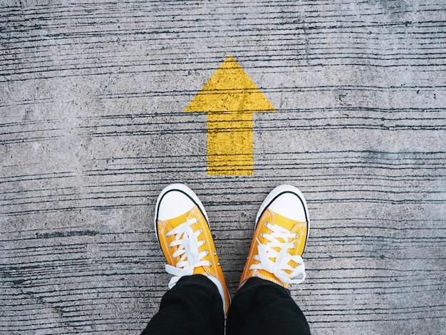 Селфи ноги носить желтые кроссовки перед стрелкой на конкретной дороге. Premium Фотографии