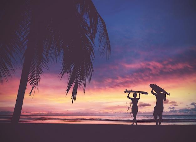 サンセットビーチでサーフボードを運ぶサーファーの人々のシルエット Premium写真