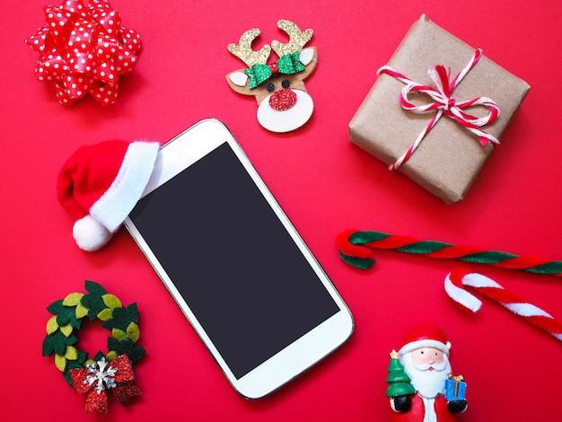 再背景にサンタクロースの帽子とクリスマスの飾りと携帯電話を閉じます。 Premium写真